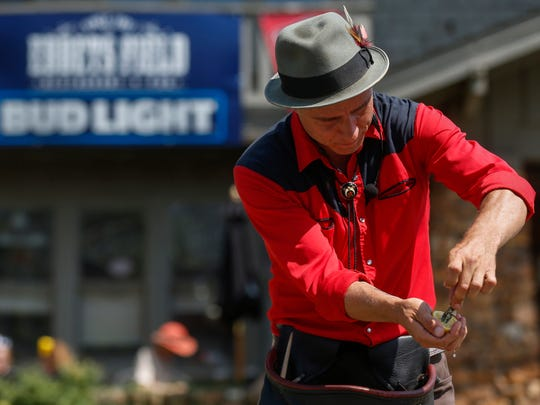 Magician Dusty Campbell pulls a $20 bill out of a lemon while performing during Artsfest on Walnut Street on Saturday, May 5, 2018.