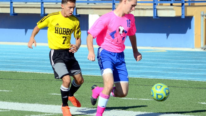 Carlsbad's Dalton Bradshaw and Hobbs' Zach Zavala chase after the ball in the first half Saturday.