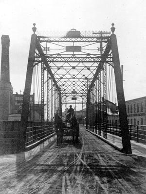 This view of the Bridge Street or Lower Bridge is looking west on Bridge or Monroe Street. As seen in the days of the horse and cart there are no paved streets. Brickner Woolen Mills is on the left and Phoenix Iron Works are on the right. The date of this photo is circa 1910. The bridge was built in 1888 by the Milwaukee Bridge and Iron Works Company.