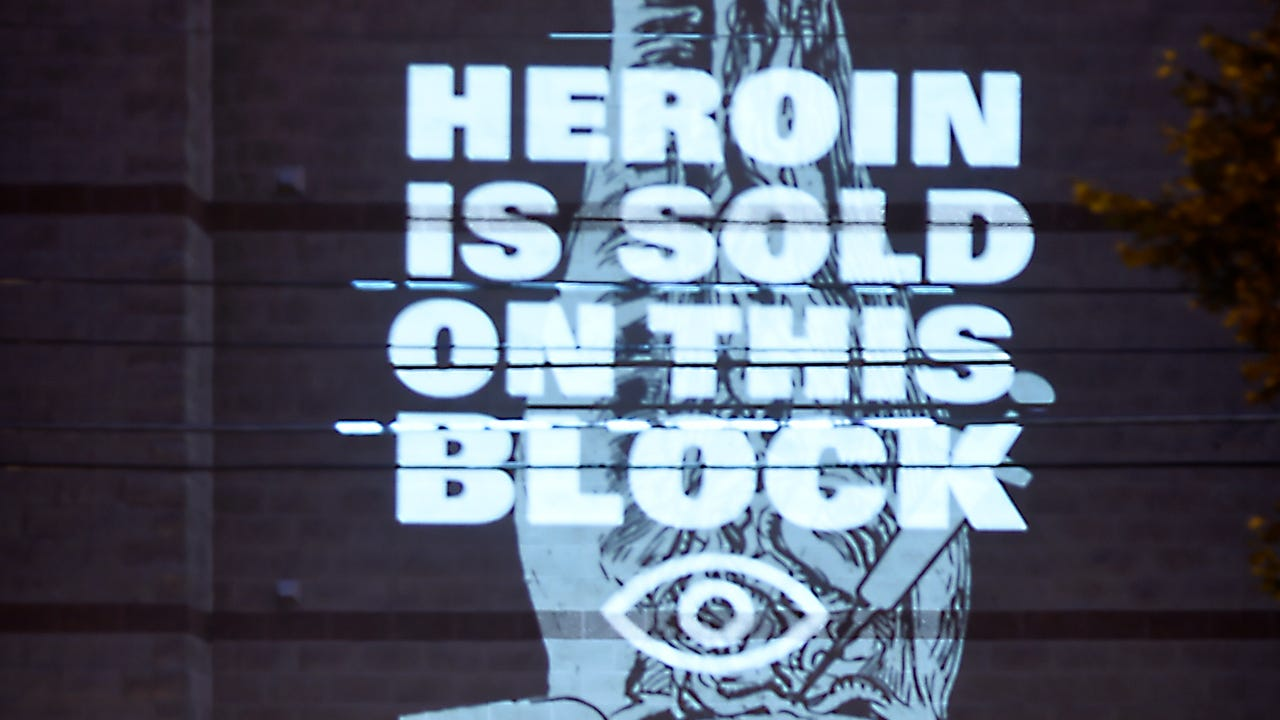 Sad statement about the Heroin epidemic is displayed on apartment building in Lebanon at Willow and 6th Street. Artist Adam DelMarcelle projects his artwork and words on local buildings.