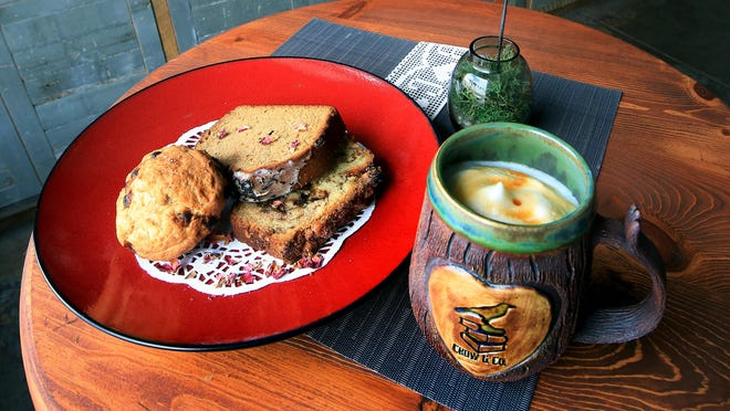 The Crow & Co. bookstore features locally sourced items in their cafe. In the handmade ceramic mug is aero au lait, an aero-pressed coffee with foamed steam milk and a flavoring, and an assortment of scones and cakes, with White Chocolate Almond, left, Earl Grey Tea cake and Amish Cinnamon bread with walnuts.