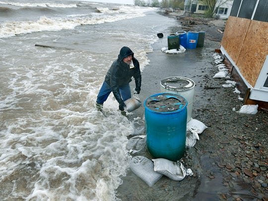Bob Jones tosses sandbags as fast as he can near his lakefront house on Sandy Harbor Drive in Hamlin. The cottage was boarded up a couple of days ago to protect it from the waves.