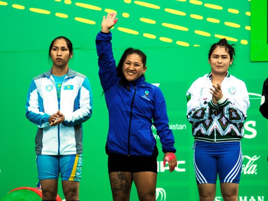 """In this file photo from September 2017, weightlifter Jacinta """"Ja"""" Sumagaysay waves to the crowd as she is introduced along with other weightlifters in the 58 kilogram class during the Asian Indoor and Martial Arts Games held September in Turkmenistan. Sumagaysay set three Guam national records during those Games."""