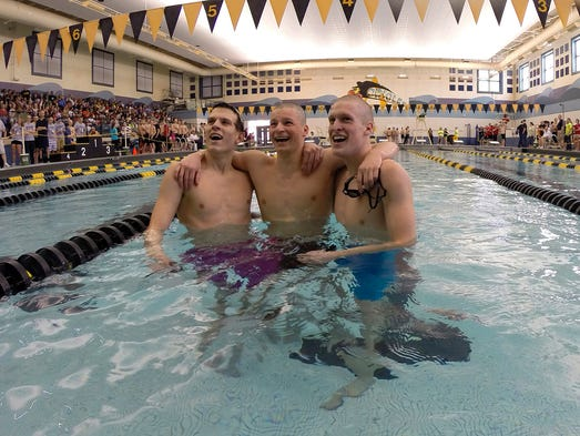 Avon High School junior Grant Lewis, middle, celebrates after winning the 200 Yard IM, finishing with a time of 1:50.97. Avon swept the podium, with sophomore Chandler Bray, left, and Greg Sprout finishing second and third. Avon High School hosted the 2014 IHSAA Boys Sectional meet Saturday, Feb. 22, 2014.