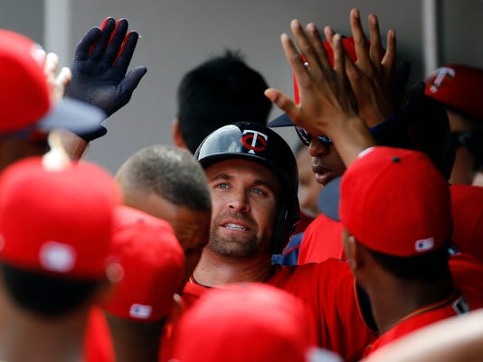Minnesota Twins' Brian Dozier, center, high-fives teammates in the dugout after hitting a solo home run in the first inning of a spring training baseball game against the Baltimore Orioles in Fort Myers, Fla., Saturday, March 5, 2016. (AP Photo/Patrick Semansky)