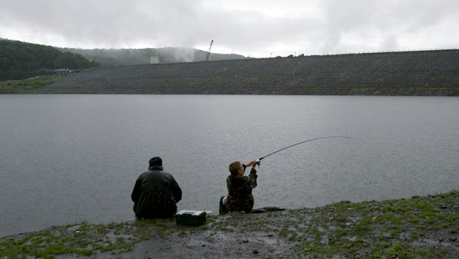Glendon Johnson, left, and his grandson, Terrick Johnson, endure the rain to do some fishing in the Waterbury Reservoir near the dam in Waterbury, Vt., Friday, June 17, 2005.(AP Photo/Toby Talbot)