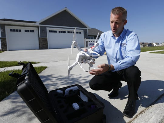 Justin Dodge, development coordinator with Hunziker Land Development unpacks his company's drone device Monday, June, 1, 2015, before taking it for a flight around one of their properties in Ames.