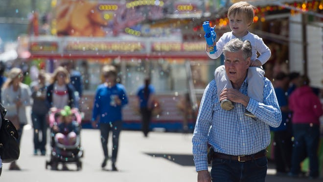 Luca Mussat, 3, makes bubbles as he rides on the shoulders of his grandpa, Charlie McCollom during Tri-Fest in downtown Henderson on Friday, April 20, 2018.