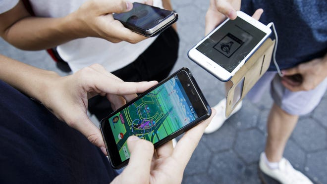 A group of people play the new game 'Pokémon Go' on their smartphones in Union Square in New York 11 July 2016. The new game was released July 8 and has players playing in a virtual world that corresponds to their actual GPS location.