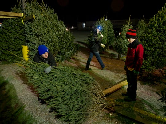 "Boy scouts from Troop 315 in Newburgh, Ind., James Oakley, 14, left, Andrew Barclay, 13, center, and Cody Oakley, 12, ""fill the cans"" with trees at their troop's Christmas tree stand on Old Indiana 261 Saturday evening. ""Push that bad boy in there. Jiggle it. Jiggle it,"" Barclay directed from nearby."