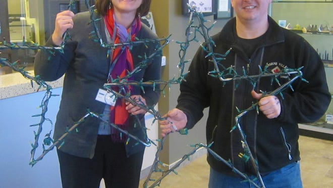 Kewaskum High School Technology & Engineering Education Department instructor Patrick Moerchen, right, presents Kondex Human Resources representative Kelly Peterson, with the holiday star decorations ordered from KHS Manufacturing.