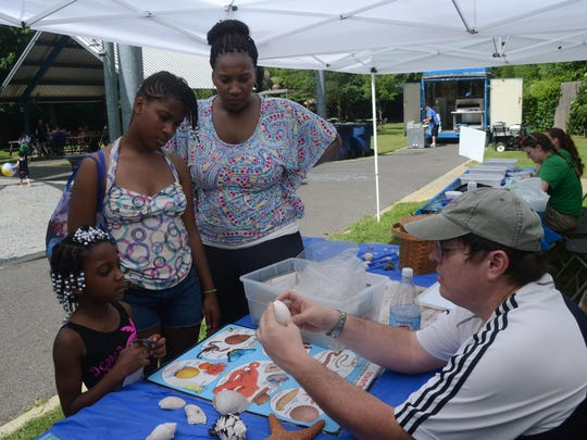 Christof Stumpf (right), a biology instructor at LSUA, gives Jamie Sykes and her niece, Nadia Sykes, and daughter Juliecia Hobdy, a lesson about starfish and mollusks at Water Play Day held Saturday.