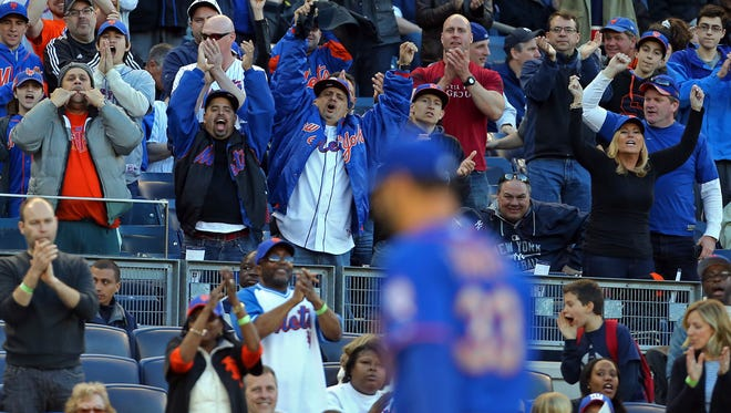 Mets fans cheer as starting pitcher Matt Harvey is taken out of the game against the Yankees at Yankee Stadium.