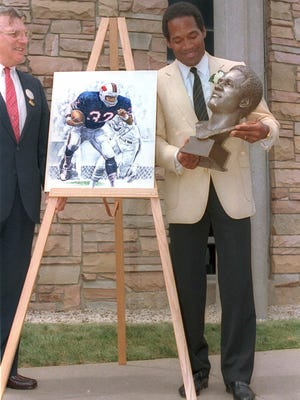O. J. Simpson checks out the bronze bust of himself after his induction into the Pro Football Hall of Fame Saturday, Aug. 3, 1985 in Canton, Ohio. Simpson played for the Buffalo Bills and later for the San Francisco 49ers during his NFL career.