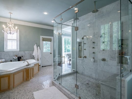 The master bathroom at 7030 East Ridge Drive includes separate stand-up shower and spa-style tub.