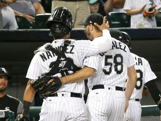 Chicago White Sox catcher Omar Narvaez, left, walks off the field with starting pitcher Miguel Gonzalez after Gonzalez retired the Houston Astros during the eighth inning of a baseball game Wednesday, Aug. 9, 2017, in Chicago. (AP Photo/Charles Rex Arbogast)