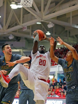 Stony Brook's Jameel Warney, center, looks to put pack on an offensive rebound against Vermont's Drew Urquhart, left, and Trae Bell-Haynes during the first half of an NCAA college basketball game in the championship of the  American East Conference men's tournament.