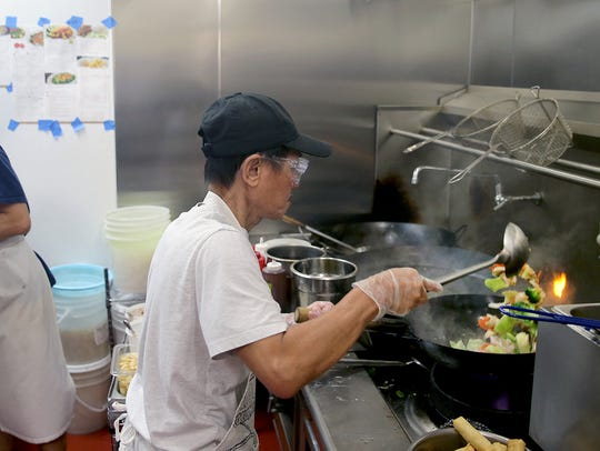 Family Thai Cuisine chef Carl Kanja mixes vegetables in a hot wok.