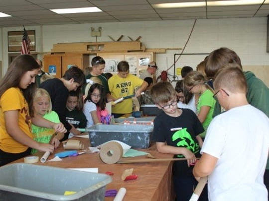 Freshmen work with fifth-graders to build rockets in