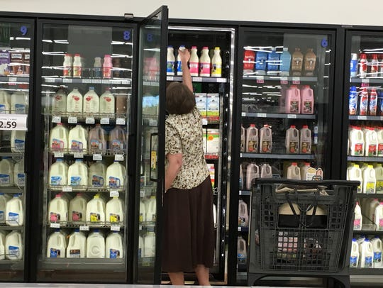 A customer reaches for milk at Festival Foods in Green