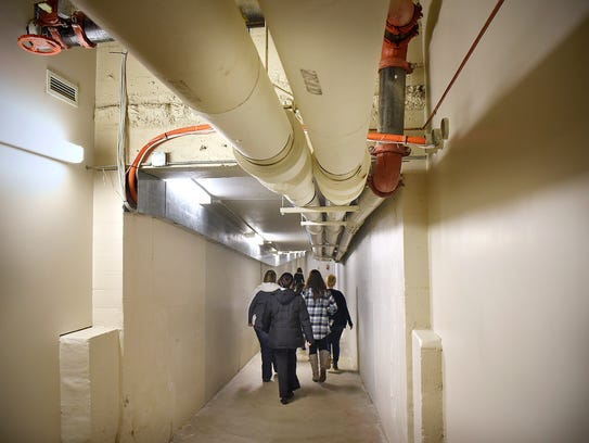 People walk down a tunnel that connects government