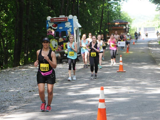 Runners exit the Walkway Over the Hudson and head toward the Town of Poughkeepsie during the inaugural Walkway Marathon on June 13, 2015.