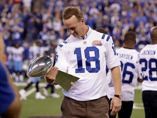 Former Indianapolis Colts quarterback Peyton Manning looks over the Vince Lombardi Trophy as the 2006 Super Bowl winning team was honored during halftime of a game in 2016.