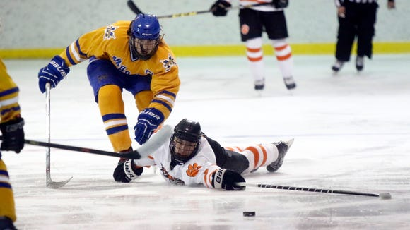 Mahopac's Chris Badnar, left, and White Plains' James Carrier battle for puck possession during their game at Ebersole Ice Rink in White Plains on Thursday.  Mahopac won 4-3.