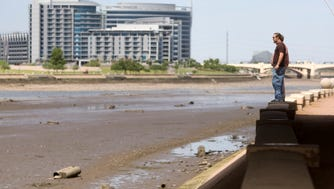 Joseph Wilmoth Jr. of Phoenix looks at the nearly completely drained Tempe Town Lake on July 21, 2010.