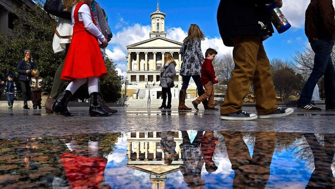 Visitors are reflected in a pool of water from rains as they walk across Legislative Plaza with the Tennessee state Capitol in the background.