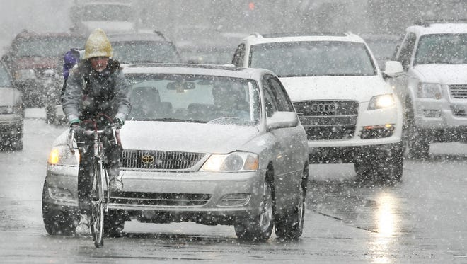 WRONG WAY: This bicyclist traveling amidst passenger cars heading north on Delaware Street at New York Street should be heading the other way -- South, toward a warmer climate and land of sun and beaches. She navigates through a heavy snow squall about 3 p.m. Monday, January 25, 2010. (Charlie Nye / The Star).