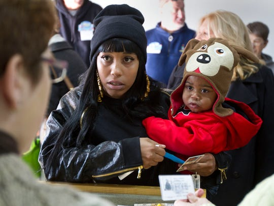 Charzena Perez and her son, Jauzon Perez, 1, of Jackson wait to receive their holiday food basket.