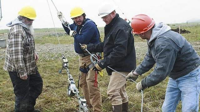 This July 2, 2011, photo provided by the U.S. Coast Guard shows Richard Belisle, second from left, and Coast Guard Electronic's Technician 1st Class James Hopkins, second from right, with Jim Wells, left, and Coast Guard Petty Officer 3rd Class Cody Beauford as they help erect a communications antenna on Shemya Island, Alaska.