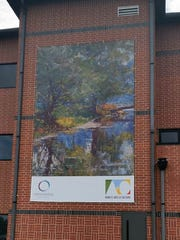A painting by Indiana artist J. Otis Adams is featured on a banner in downtown Muncie.