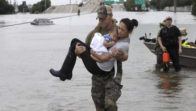 Houston Police SWAT officer Daryl Hudeck carries Catherine Pham and her son Aiden after rescuing them from their home.