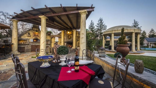 Patti and Keith Webb of Palo Cedro have a commercial-size pizza oven built beside a covered pavilion, complete with sitting area and large faux stone fireplace.