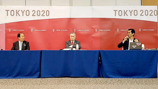 In this image made from video provided by Tokyo 2020 Official YouTube Channel, Tokyo 2020 Olympics President Yoshiro Mori, center, with CEO Toshiro Muto, left, attends a press conference after an IOC executive board meeting in Tokyo, Wednesday, June 10, 2020.