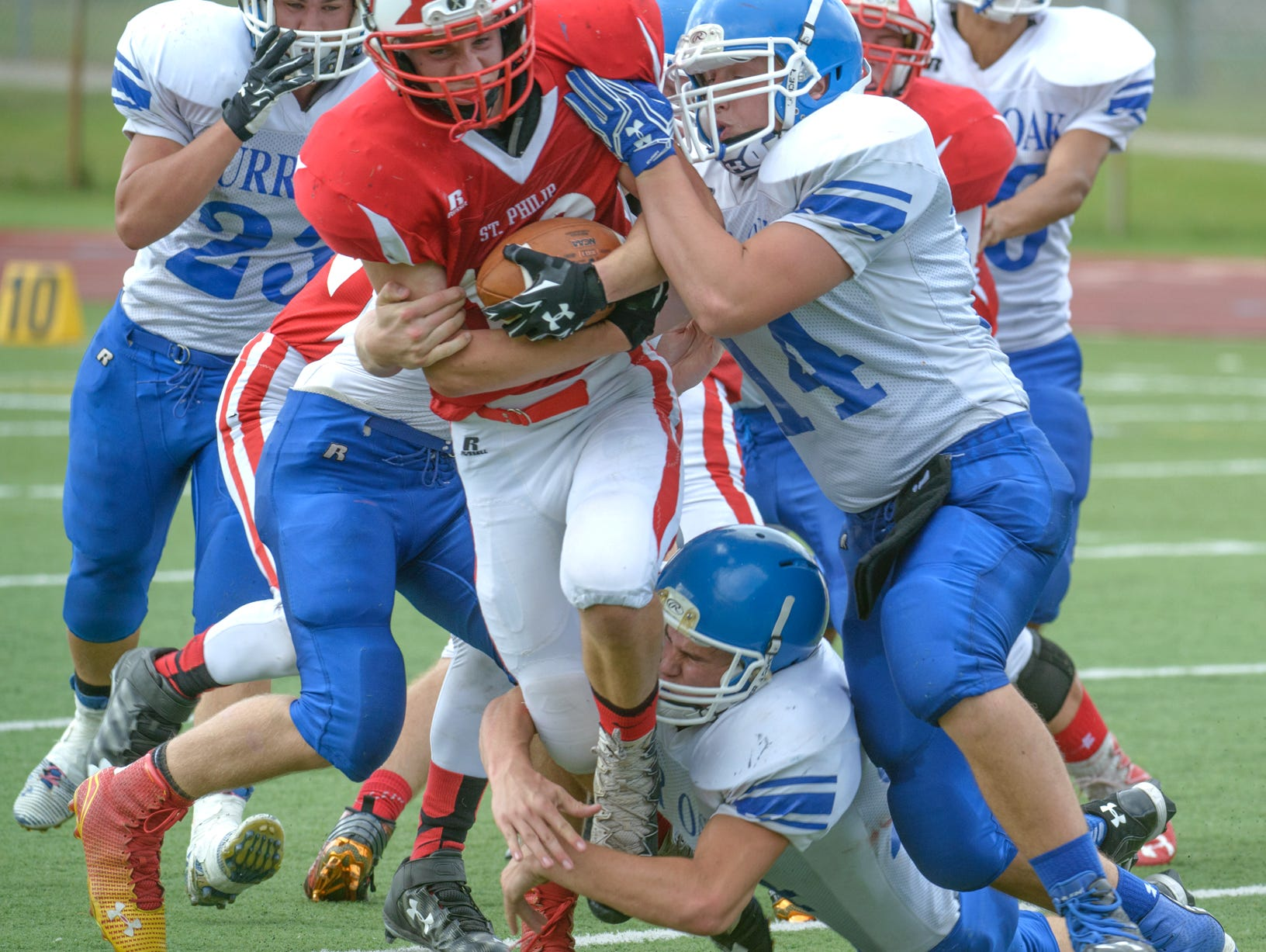 St. Philip tight end Grayson Obey (16) powers through Burr Oak defenders for positive yards Saturday afternoon.