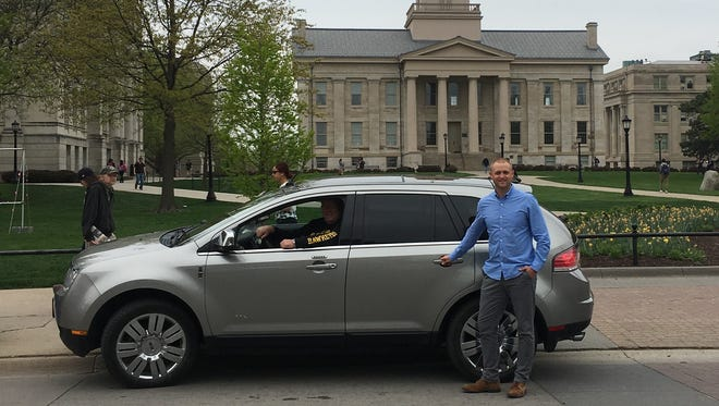 Nate Kaeding, retail development director for the Downtown District, poses with an Uber car at the Pentacrest.