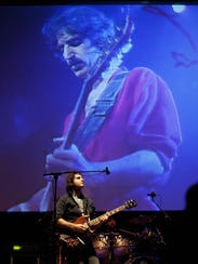 Dweezil Zappa performs in front of a projection of