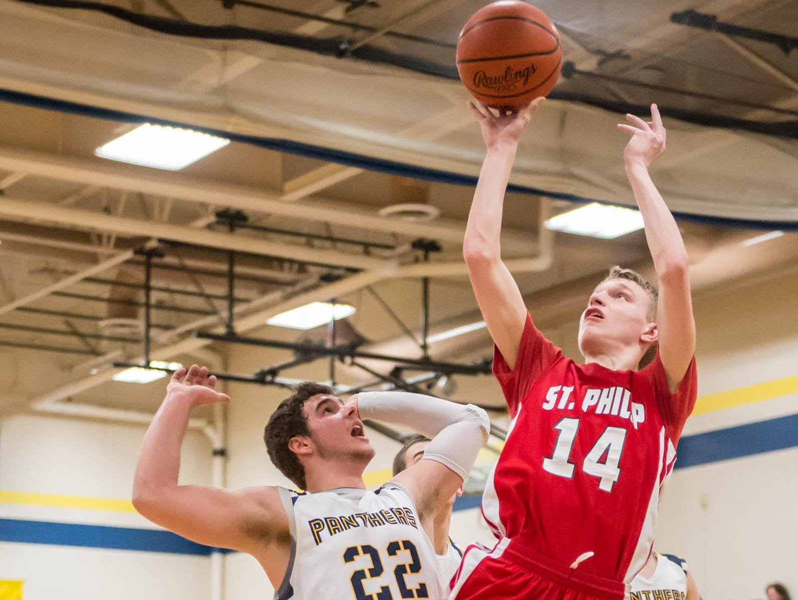 St. Philip's Justice Steiner (14) goes up for a shot over a Climax-Scotts defender in action earlier this season.