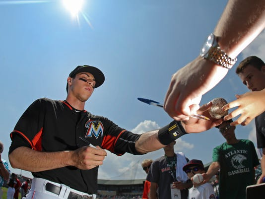 Miami Marlins left fielder Christian Yelich (21) signs autographs before an exhibition spring training baseball game against the Washington Nationals Wednesday, March 18, 2015, in Jupiter, Fla.  (AP Photo/John Bazemore)