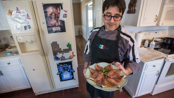 Chef Salvatore Arru shows a sardine dish he's marinating for lunch Sunday, Jan. 16, at his home in St. Clair.
