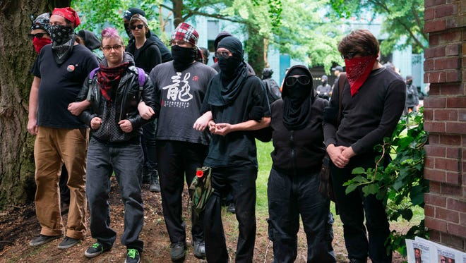 Far-left antifa demonstrators link arms at Chapman Square during a protest against President Trump in downtown Portland June 4, 2017, as police attempt to move them away from the square.