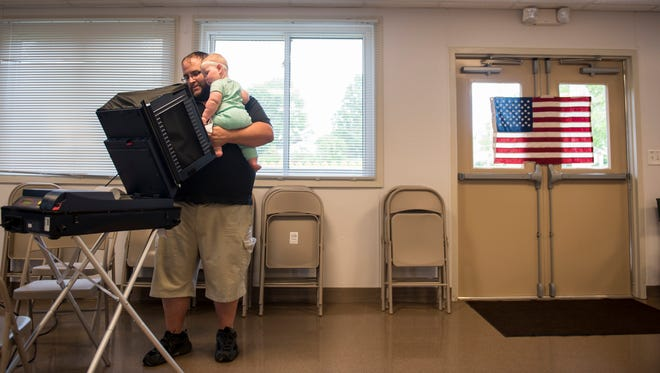 Chris Miller holds his daughter, Charlotte, 7 months old, while voting at a polling station at the Utz Pavilion for Hanover Borough's Third Ward on Tuesday.