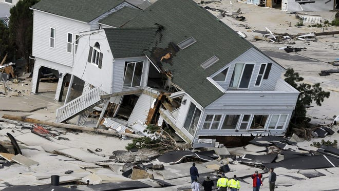 People survey destruction left in the wake of superstorm Sandy, Oct. 31, 2012, in Seaside Heights.
