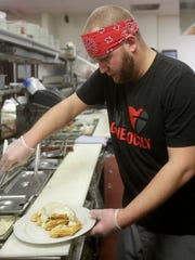 Chef Adam Steinke prepares a dish of chicken and waffles Sunday at Great Dane Pub in Wausau.