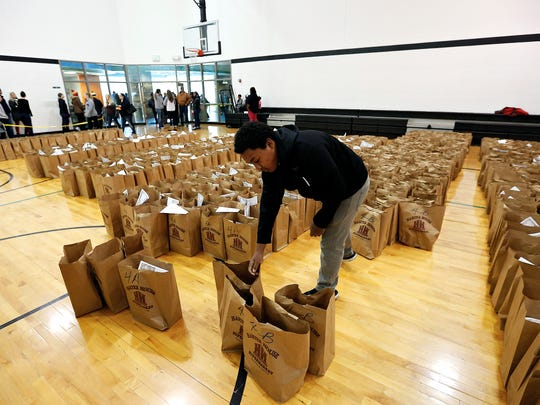 Marcus Young, 14, organizes grocery bags that will be handed out to families during a Thanksgiving meal distribution event organized by Crosslines and held at Central Assembly Church in Springfield, Mo. on Nov. 19, 2016.