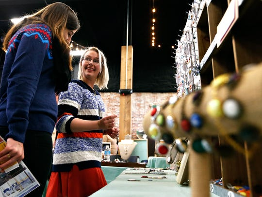 Pauline (left) and Michelle Gonzalez look at jewelry in the Little Wendy Bird booth during this year's Queen City Craft Show, held at The Old Glass Place in Springfield, Mo. on Nov. 26, 2016.