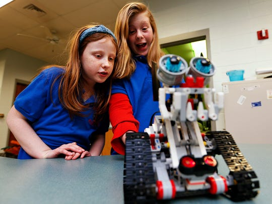 Robotics Club members Ashlee Parks, left, 9, and Parker Gamet, 10, show off their dog-like robot during the STEAM Night event held at McBride Elementary School in Springfield, Mo. on Feb. 2, 2017. The robots were acquired by McBride thanks to a grant from the Foundation for Springfield Public Schools.